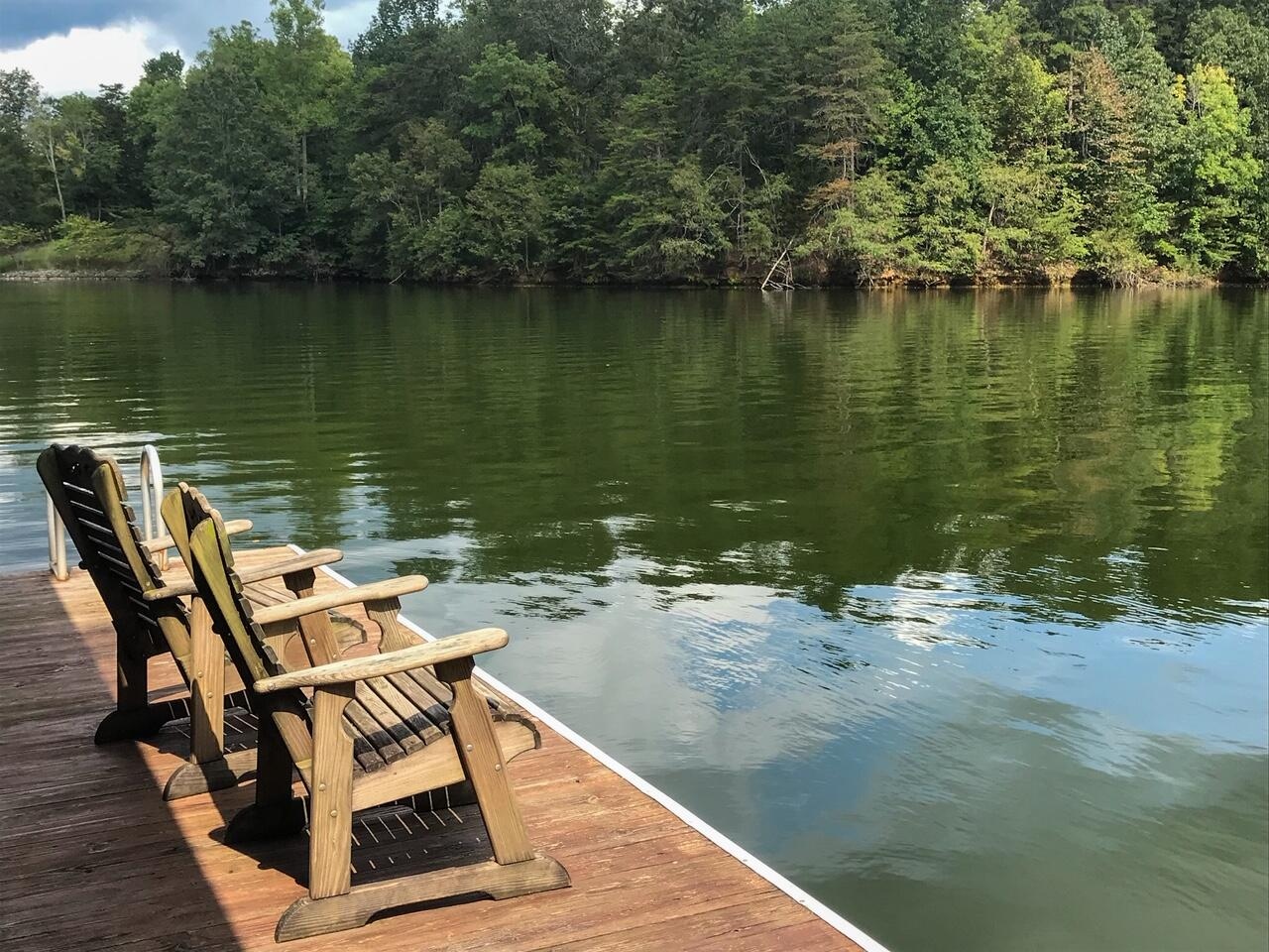 Two chairs on a dock on the lake
